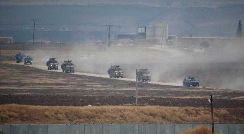 FILE PHOTO: Turkish and Russian military vehicles return following a joint patrol in northeast Syria, as they are pictured from near the Turkish border town of Kiziltepe