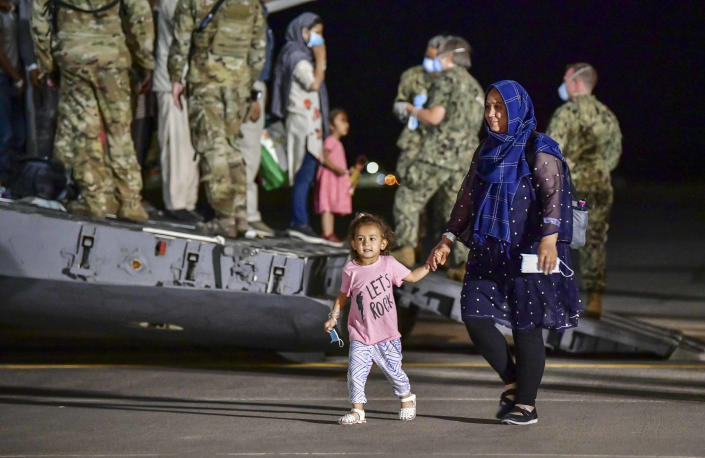 CORRECTS PHOTOGRAPHER TO DANIEL YOUNG - Evacuees from Afghanistan disembark from a U.S. Air Force C-17 Globemaster III at the Sigonella US air base, in Sicily, southern Italy, Sunday, Aug. 22, 2021. People fleeing Afghanistan arrived at the U.S. naval air base in Sicily as Washington tried to ramp up evacuations following the Taliban takeover of the country by using overseas military bases as temporary transit points. (Daniel Young/U.S. Navy via AP)