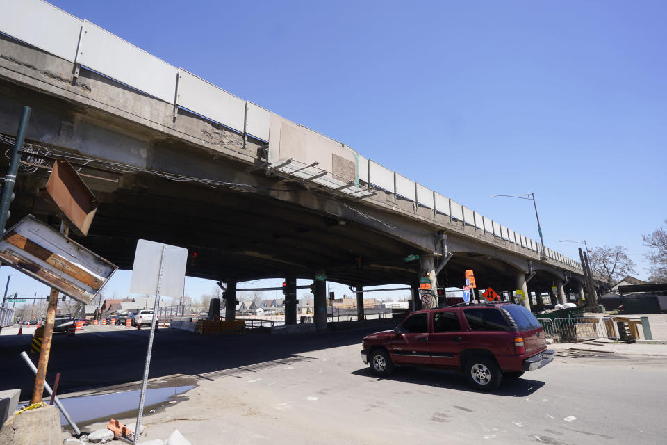 In this Thursday, April 29, 2021, photograph, a motorist heads under the crumbling elevated portion of Interstate 70 set to be replaced as part of the Central 70 Project workers north of downtown Denver. The elevated roadway that has served as Interstate 70 will be demolished as part of the 10-mile-long project, which will cost $1.2 billion by completion by winter 2022. (AP Photo/David Zalubowski)