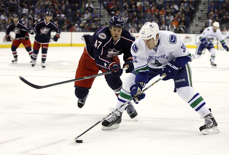 Columbus's Dalton Prout (47) chases down Vancouver's Dale Weise during the first period of an NHL hockey game Sunday, Oct. 20, 2013, in Columbus, Ohio. (AP Photo/ Mike Munden)