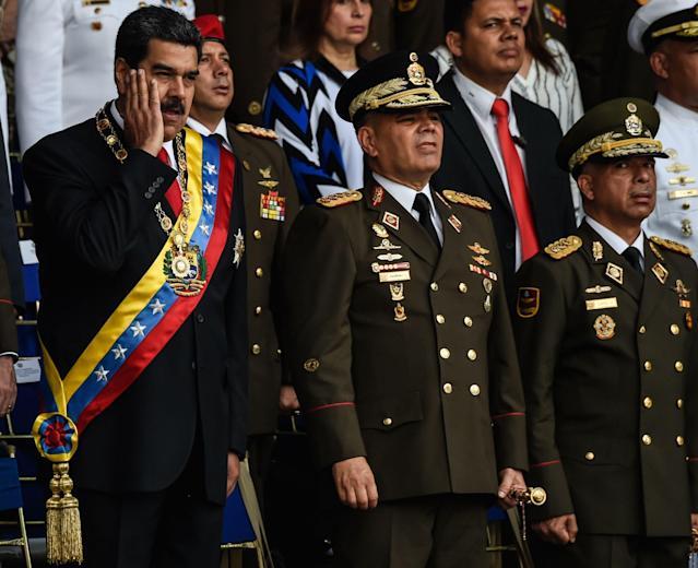 <p>Venezuelan President Nicolas Maduro (L) gestures next to Minister of Defence General Vladimir Padrino (C), during a ceremony to celebrate the 81st anniversary of the National Guard in Caracas on August 4, 2018. (Photo: Juan Barreto/AFP/Getty Images) </p>