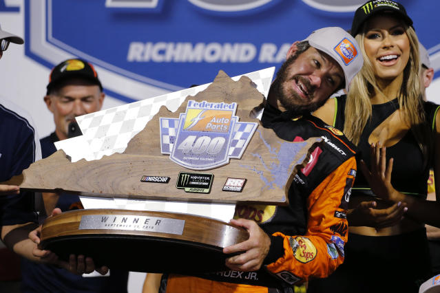 Martin Truex Jr. struggles to lift the winner's trophy after his victory in the NASCAR Cup Series auto race at Richmond Raceway in Richmond, Va., Saturday, Sept. 21, 2019. (AP Photo/Steve Helber)
