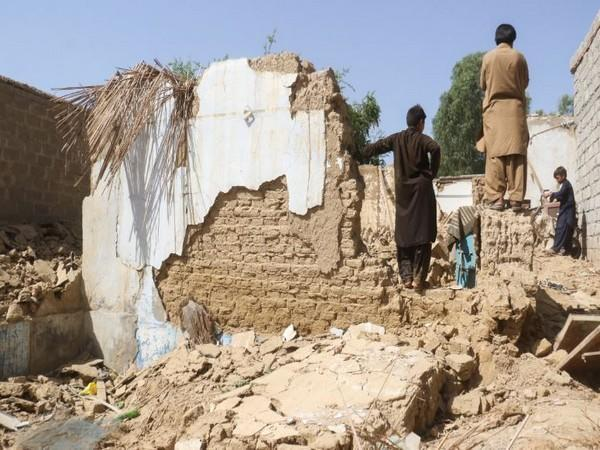 Residents stand amid the rubble of a damaged house following an earthquake in Harnai, Balochistan