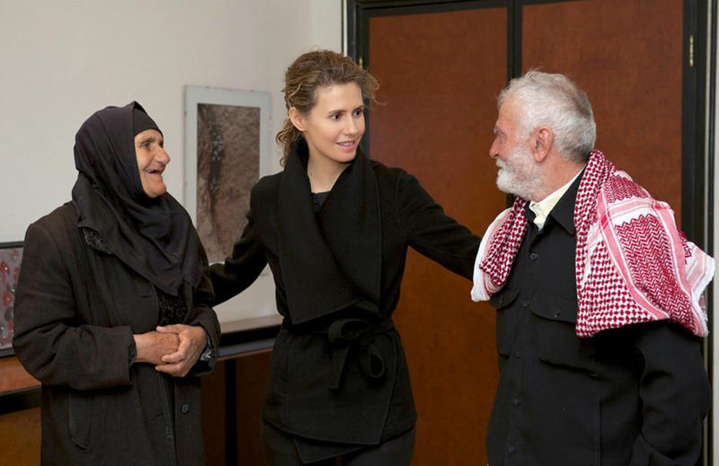 CAPTION CORRECTION, CORRECTS TO SAY PHOTO IS UNDATED - In this undated photo released Thursday, July 11, 2013, Syria's first lady Asma Assad, center, talks with families of the country's armed and security forces who were killed during the civil war in Damascus, Syria. Syrian President Bashar Assad set up a committee that will be in charge of taking care of all legal measures regarding families of Syrian troops killed in the fighting against rebels. (AP Photo, Syrian Presidency)