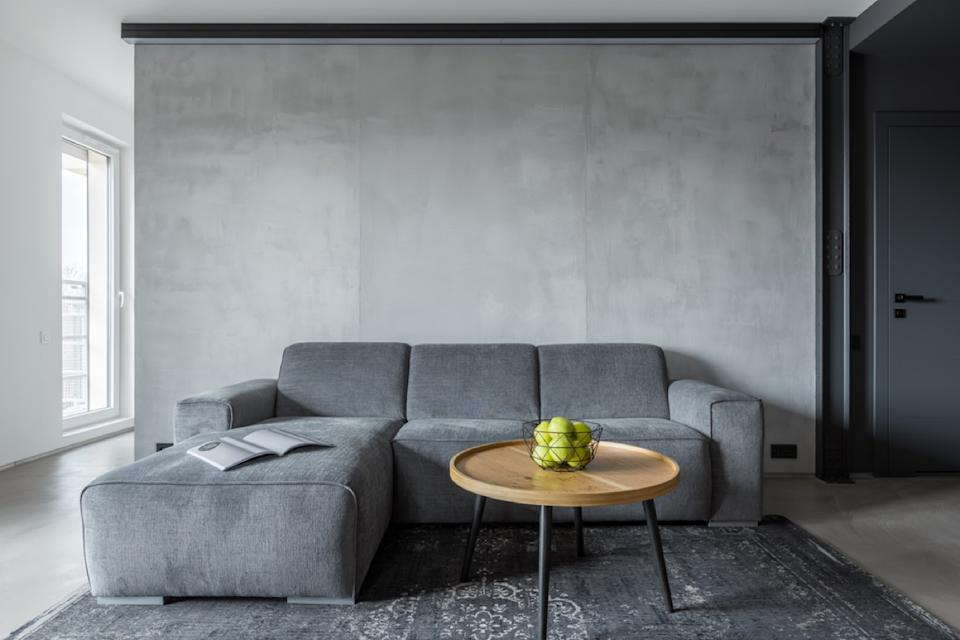 gray living room with gray walls, gray couch, and circular wooden table