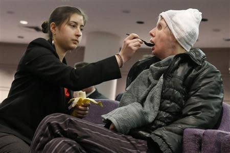 Charla Nash (R) is helped by her daughter Briana Nash to eat a banana during her hearing at the Legislative Office Building in Hartford, Connecticut, March 21, 2014. REUTERS/Eduardo Munoz