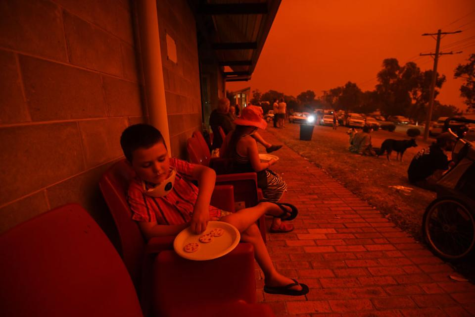 A boy eats biscuits while sitting amid a red and orange sky in Mallacoota.