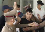 FILE - In this Aug, 26, 2020, file photo, a student protest leader Tattep Ruangprapaikitseree raises a three-finger salute, a symbol of resistance, as he leaves a police station for a court appearance in Bangkok, Thailand. Fed up with an archaic educational system and enraged by the military's efforts to keep control over their nation, a student-led campaign has shaken Thailand's ruling establishment with the most significant campaign for political change in years. (AP Photo/Sakchai Lalit, File)