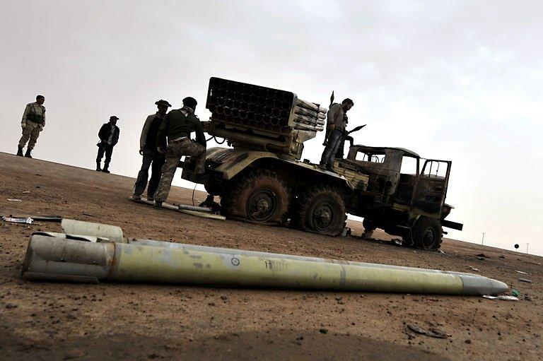 Libyan rebels stand with a missile launcher in the eastern city of Ajdabiya. Libyan leader Moamer Kadhafi suffered a major blow Wednesday with the defection of his foreign minister even as his forces again proved too strong for the rebels' rag-tag army