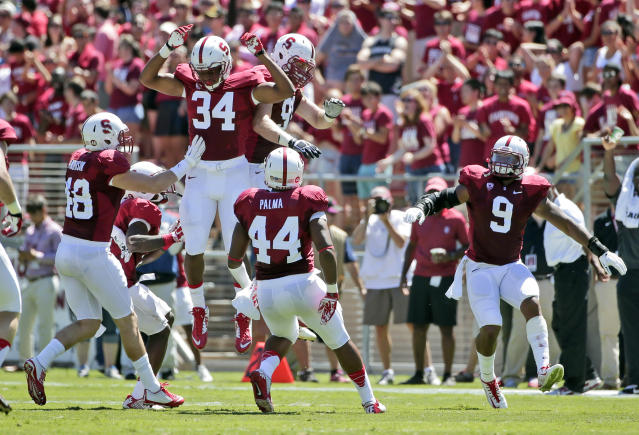 Stanford 's Peter Kalambayi (34) celebrates his interception with teammates during the first half of an NCAA college football game against UC Davis on Saturday, Aug. 30, 2014, in Stanford, Calif. (AP Photo/Marcio Jose Sanchez)