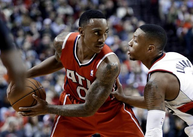 Atlanta Hawks guard Jeff Teague, left, looks for an opening against Portland Trail Blazers guard Damian Lillard during the first half of an NBA basketball game in Portland, Ore., Wednesday, March 5, 2014. (AP Photo/Don Ryan)
