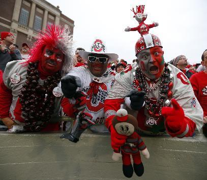Ohio State fans Larry Lokai, left, John Chubb, center, and Jon P. Peters, right, celebrate after a Buckeye touchdown during the second half of an NCAA college football game against Illinois on Saturday, Nov. 16, 2013, in Champaign, Ill. Ohio State won the game 60-35. (AP Photo/Jeff Haynes)