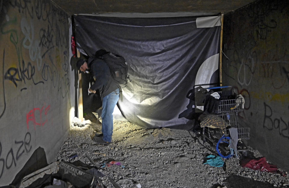 FILE - In this Dec. 5, 2020, file photo, Paul Vautrinot of Shine a Light passes though personal belongs as he provides outreach in the underground tunnels to offer counseling, food and water to the homeless living beneath the city in Las Vegas. When census takers tried to count the nation's homeless population, they ran into many problems that could threaten the accuracy of the effort. That's what a half dozen census takers around the U.S. tell The Associated Press. (AP Photo/David Becker, File)