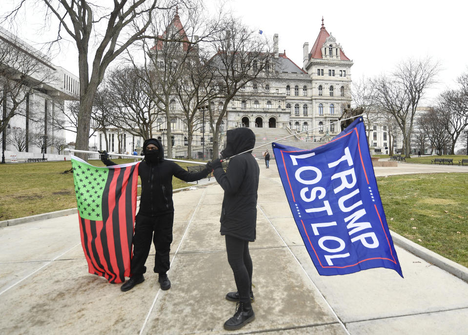 """A supporter from Black Liberation, left, and one from the group """"All Of Us' hold flags while counter protesting a Trump rally ahead of the inauguration of President-elect Joe Biden and Vice President-elect Kamala Harris at the New York state Capitol Sunday, Jan. 17, 2021, in Albany, N.Y. (AP Photo/Hans Pennink)"""