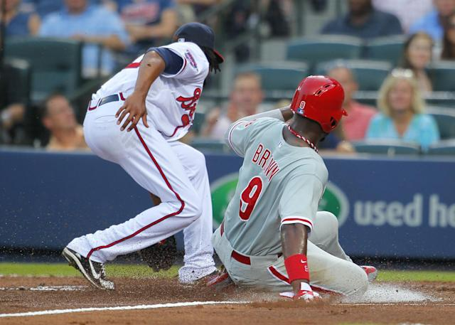 Philadelphia Phillies Domonic Brown, right, slides into home after a wild pitch by Atlanta Braves starting pitcher Ervin Santana, left, in the fourth inning of a baseball game Tuesday, June 17, 2014, in Atlanta. (AP Photo/Todd Kirkland)