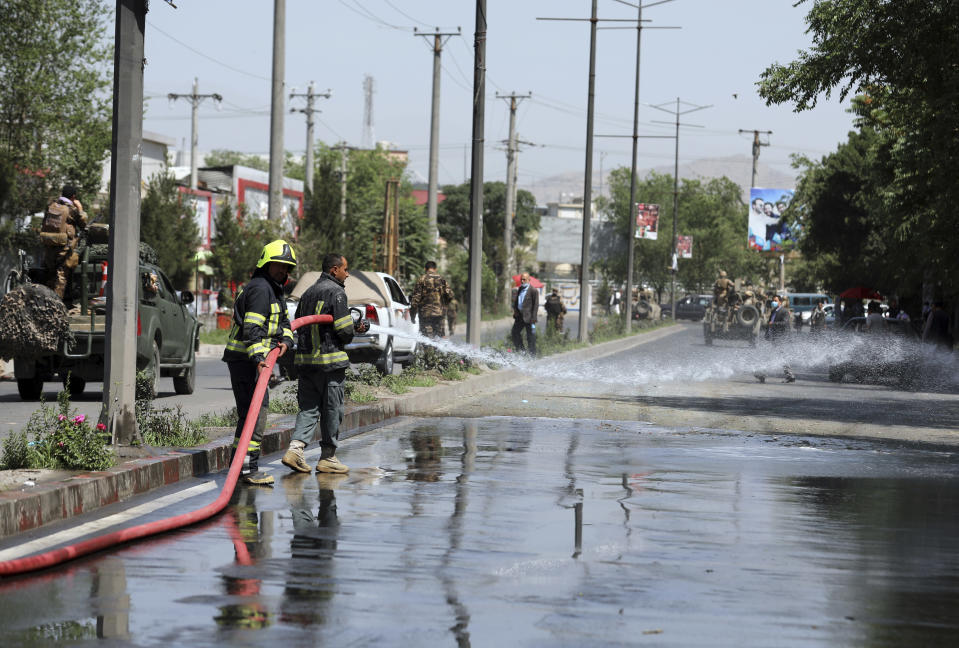 Afghan firefighters spray water at the scene of a roadside bomb explosion in Kabul, Afghanistan, Sunday, June 6, 2021. (AP Photo/Rahmat Gul)