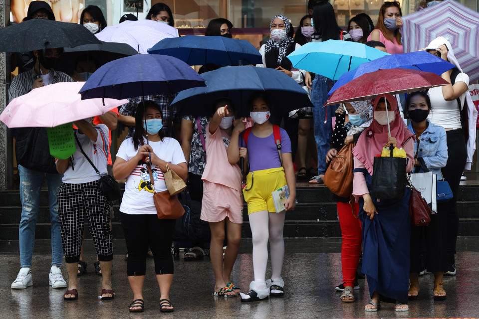 SINGAPORE - JANUARY 10: People wearing protective masks wait to cross a street in the rain on January 10, 2021 in Singapore. As of January 10, the Ministry of Health confirmed 42 new imported COVID-19 cases, with zero cases in the wider community bringing the country's total to 58,907. (Photo by Suhaimi Abdullah/Getty Images)