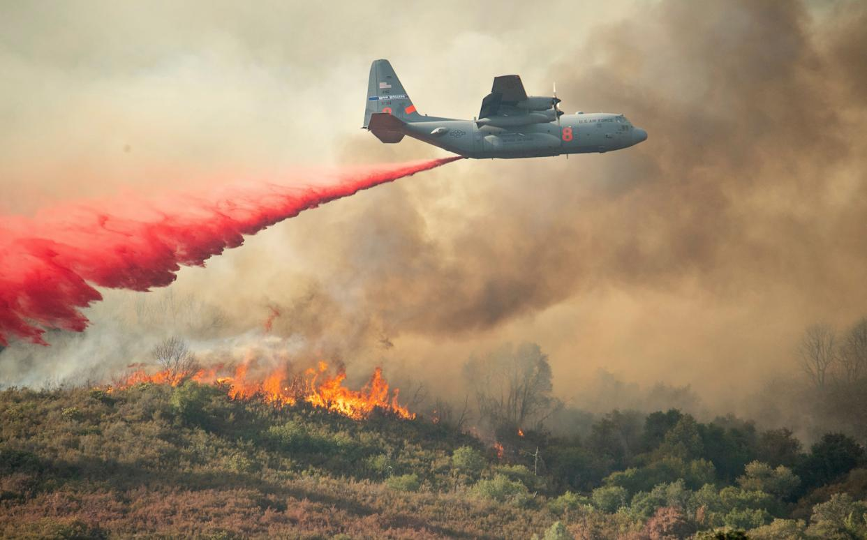 A U.S. Air Force plane drops fire retardant on a burning hillside in the Ranch Fire.