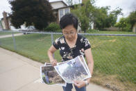 """Bobbie Uno displays photographs of burnt brushes outside her home Thursday, June 24, 2021, in Clearfield, Utah. July Fourth fire works are a mainstay summer tradition for Americans aching for normalcy as pandemic restrictions ease, but the megadrought gripping the West means the colorful sparklers and exploding bottle rockets could be seriously dangerous. They also carry risk, starting thousands of fires a year - including one that burned Uno's home on the holiday last year. """"Within five seconds my house, from the bushes to the rooftop, it was burning,"""" she said. (AP Photo/Rick Bowmer)"""