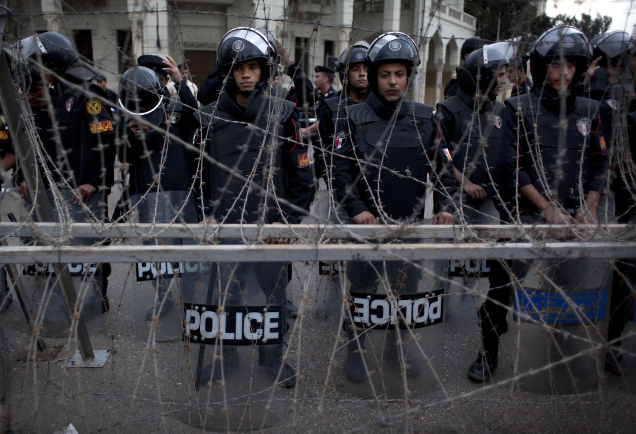 Egyptian riot police stand guard behind barbed wire while protesters chant anti Muslim Brotherhood slogans, not pictured, during a demonstration in front of the presidential palace, in Cairo, Egypt, Tuesday, Dec. 4, 2012. Thousands of Egyptians massed in Cairo Tuesday for a march to the presidential palace to protest the assumption by the nation's Islamist president of nearly unrestricted powers and a draft constitution hurriedly adopted by his allies. (AP Photo/Nasser Nasser)