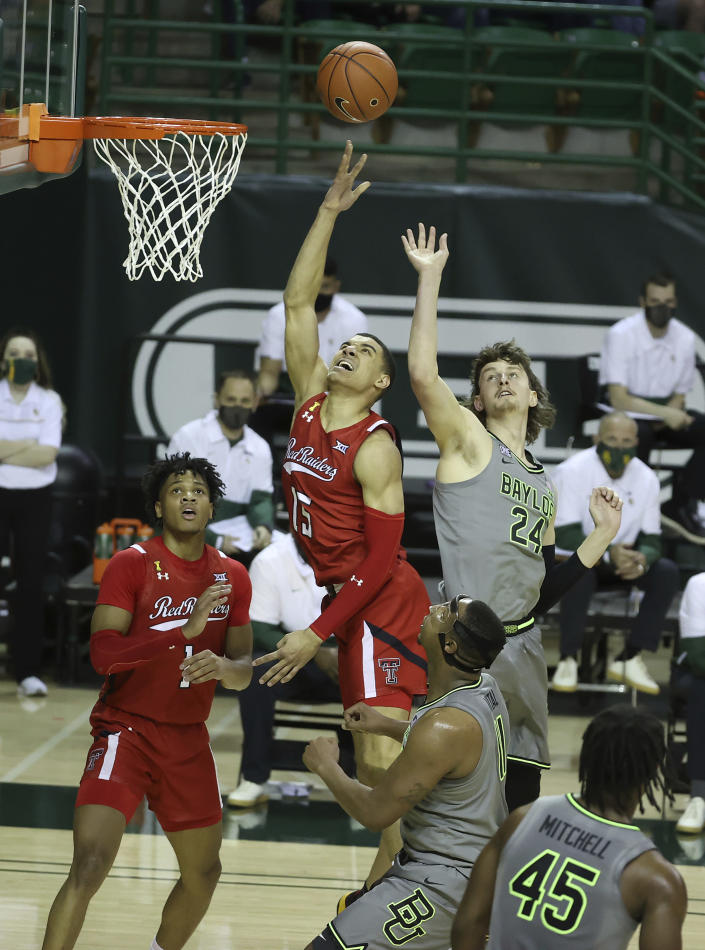 Texas Tech guard Kevin McCullar (15) attempts a shot past Baylor guard Matthew Mayer (24) in the first half of an NCAA college basketball game Sunday, March 7, 2021, in Waco, Texas. (AP Photo/Jerry Larson)