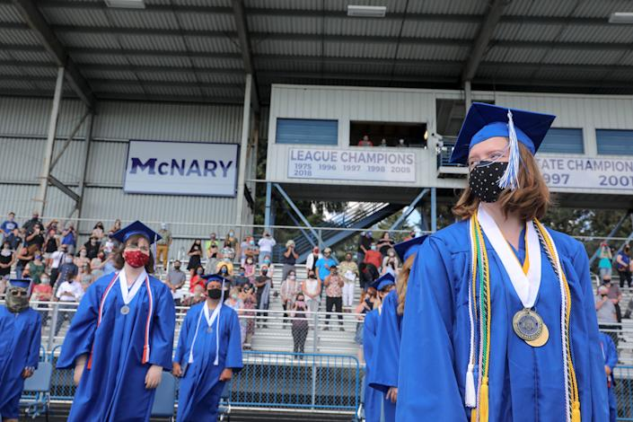 Students move their tassels and prepare to leave the field following a graduation ceremony at McNary High School in Keizer, Ore., on Aug. 7, 2020.