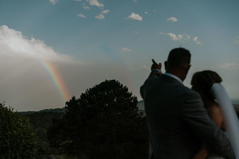 A silhouette shot of the bride and groom outdoors. The groom has his right arm wrapped around the bride as he points to a rainbow in the distance.  (James Day Photography)