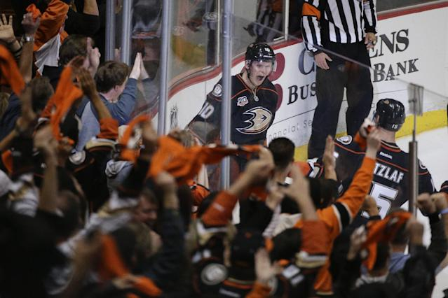 The fans cheer as Anaheim Ducks' Corey Perry, center, and Ryan Getzlaf celebrate a goal by Perry during the second period in Game 2 of the first-round NHL hockey Stanley Cup playoff series against the Dallas Stars on Friday, April 18, 2014, in Anaheim, Calif. (AP Photo/Jae C. Hong)