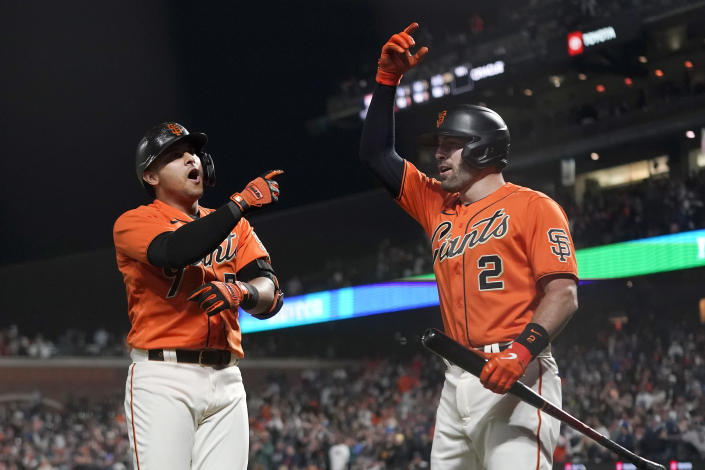 San Francisco Giants' Donovan Solano, left, celebrates with Curt Casali after hitting a home run against the Atlanta Braves during the ninth inning of a baseball game in San Francisco, Friday, Sept. 17, 2021. (AP Photo/Jeff Chiu)