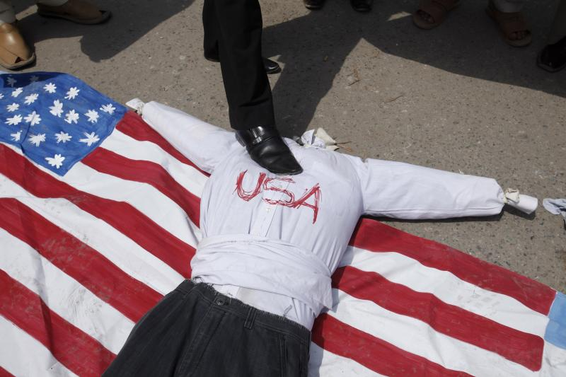 A Shi'ite Muslim places his foot upon an effigy symbolizing the U.S. and the U.S. national flag while protesting with others against the Arab League and possible U.S. attacks on Syria, in Peshawar