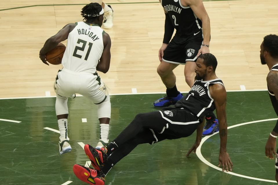 Milwaukee Bucks' Jrue Holiday is called for a charge on Brooklyn Nets' Kevin Durant during the first half of Game 4 of the NBA Eastern Conference basketball semifinals game Sunday, June 13, 2021, in Milwaukee. (AP Photo/Morry Gash)