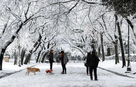 People walk at Villa Borghese during a heavy snowfall in Rome, Italy February 26, 2018. REUTERS/Remo Casilli