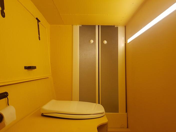 The yellow bathroom aboard the double decker bus with a toilet and shower