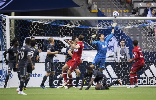 Vancouver Whitecaps goalkeeper Brian Rowe (12) reaches for the ball as it strikes the crossbar and stays out of the net, off the head of Chicago Fire's Jonathan Campbell (16) during the second half of a Major League Soccer match Saturday, July 7, 2018, in Vancouver, British Columbia. (Darryl Dyck/The Canadian Press via AP)