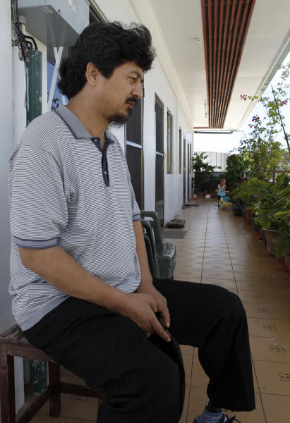 In this photo taken on Feb. 9, 2013, former Guantanamo prisoner Ahmat Abdulahad sits outside a fellow refugee's small apartment in Koror, Palau. Released from Guantanamo Bay military prison by the U.S. in 2009, Abdulahad and several other Uighur men have been struggling on the South Pacific island nation of Palau where they have been temporarily resettled. The men and Palau's new president say pressure from China has made it impossible for them to find a permanent home elsewhere. (AP Photo/Eric Talmadge)