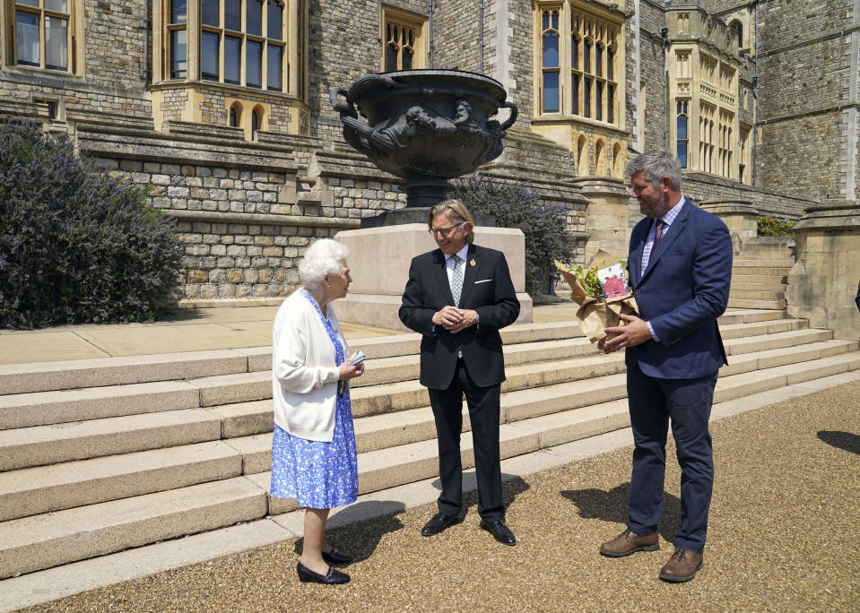 Britain's Queen Elizabeth II receives a Duke of Edinburgh rose, with Keith Weed, centre, President of the Royal Horticultural Society, at Windsor Castle, England, Wednesday June 9, 2021. The newly bred deep pink commemorative rose has officially been named in memory of the late Prince Philip Duke of Edinburgh. A royalty from the sale of each rose will go to The Duke of Edinburgh's Award Living Legacy Fund to support young people taking part in the Duke of Edinburgh Award scheme. (Steve Parsons/Pool via AP)