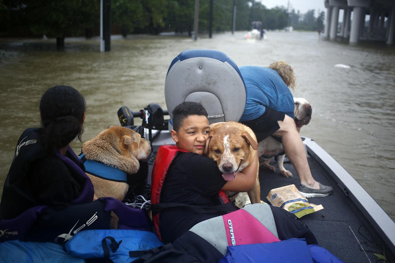 <p>A boy hugs his grandmothers' dog after being rescued from rising floodwaters due to Hurricane Harvey in Spring, Texas, on Aug. 28, 2017. A deluge of rain and rising floodwaters left Houston immersed and helpless, crippling a global center of the oil industry and testing the economic resiliency of a state thats home to almost 1 in 12 U.S. workers. (Photo: Luke Sharrett/Bloomberg via Getty Images) </p>