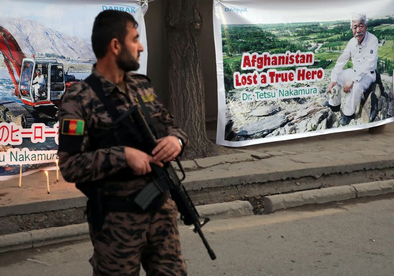 An Afghan security force stands guard in front of a poster depicting Japanese doctor Tetsu Nakamura, who was killed in Jalalabad in yesterday's attack, in Kabul