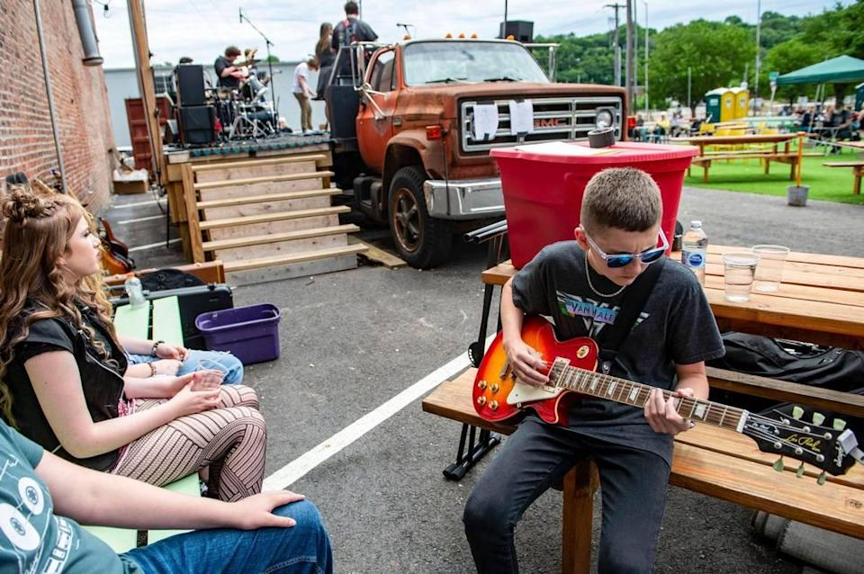 As part of Make Music Kansas City, Sawyer Lane tunes and plays a little bit on a guitar before performing on stage with the rest of the School of Rock Kansas City House Band, Monday, June 21, 2021 at Lemonade Park in Kansas City. The musical event was one of over 70 free performances held as Kansas City made its' debut on Make Music Day, a world-wide celebration of music happening in over 1,000 cities in 120 countries.