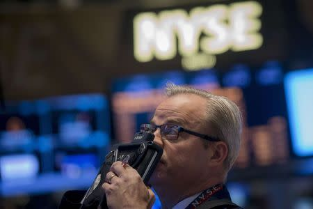 A trader looks up at a screen on the floor of the New York Stock Exchange