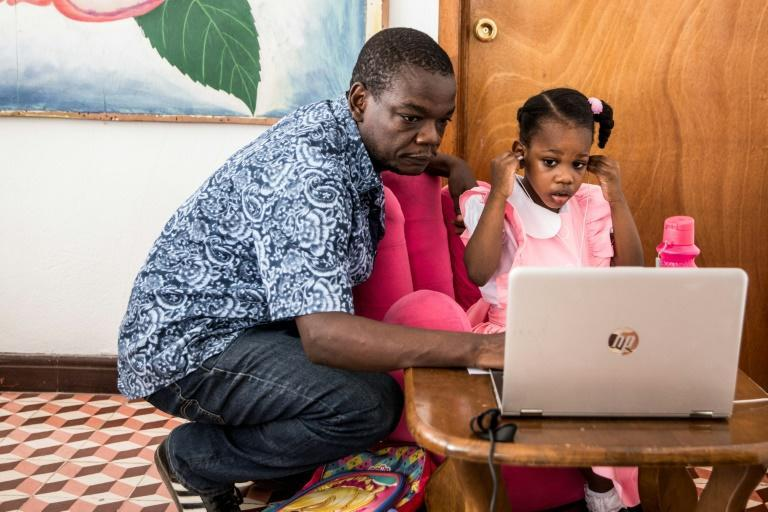 Jean Romuald Ernest, 47, helps his daughter Lucie reconnect to the internet; most schools in Port-au-Prince have been closed but many Haitians lack computers or internet access