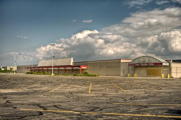 Abandoned shopping center in empty parking lot during the day