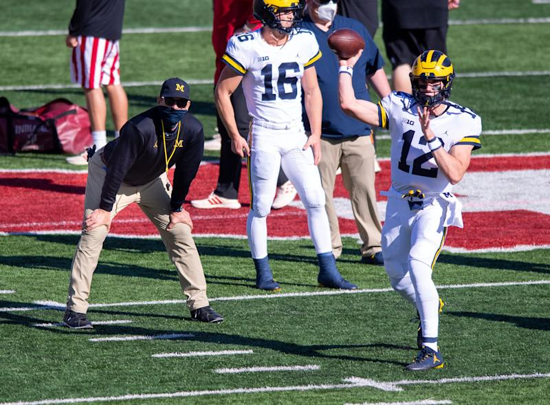 Michigan coach Jim Harbaugh, left, watches as quarterback Cade McNamara warms up before the game against Indiana, Saturday, Nov. 7, 2020, in Bloomington, Ind.