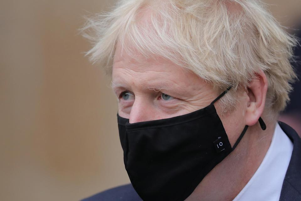 Britain's Prime Minister Boris Johnson, wearing a protective face covering to combat the spread of the coronavirus, leaves after attending a service to mark the centenary of the burial of the unknown warrior at Westminster Abbey in central London, on November 11, 2020. - The Armistice Day service commemorates the funeral of an unknown British serviceman, the Unknown Warrior, whose body was brought from Northern France and buried at the west end of the nave on 11th November 1920 to represent all those who lost their lives in the First World War but whose place of death was not known, or whose bodies remained unidentified. (Photo by Aaron Chown / POOL / AFP) (Photo by AARON CHOWN/POOL/AFP via Getty Images)