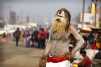 A Hindu holy man watches pilgrims walk past during Magh Mela festival, in Prayagraj, India. Tuesday, Feb.16, 2021. Millions of people have joined a 45-day long Hindu bathing festival in this northern Indian city, where devotees take a holy dip at Sangam, the sacred confluence of the rivers Ganga, Yamuna and the mythical Saraswati. Here, they bathe on certain days considered to be auspicious in the belief that they be cleansed of all sins. (AP Photo/Rajesh Kumar Singh)
