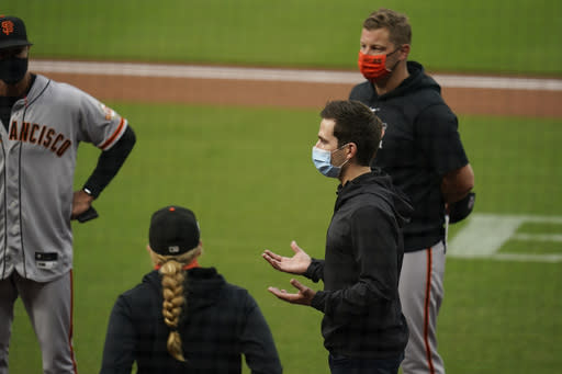 San Francisco Giants general manager Scott Harris, second from right, speaks to members of the team after their baseball game against the San Diego Padres was postponed Friday, Sept. 11, 2020, in San Diego. The game was postponed minutes before the scheduled first pitch after someone in the Giants organization tested positive for COVID-19. (AP Photo/Gregory Bull)