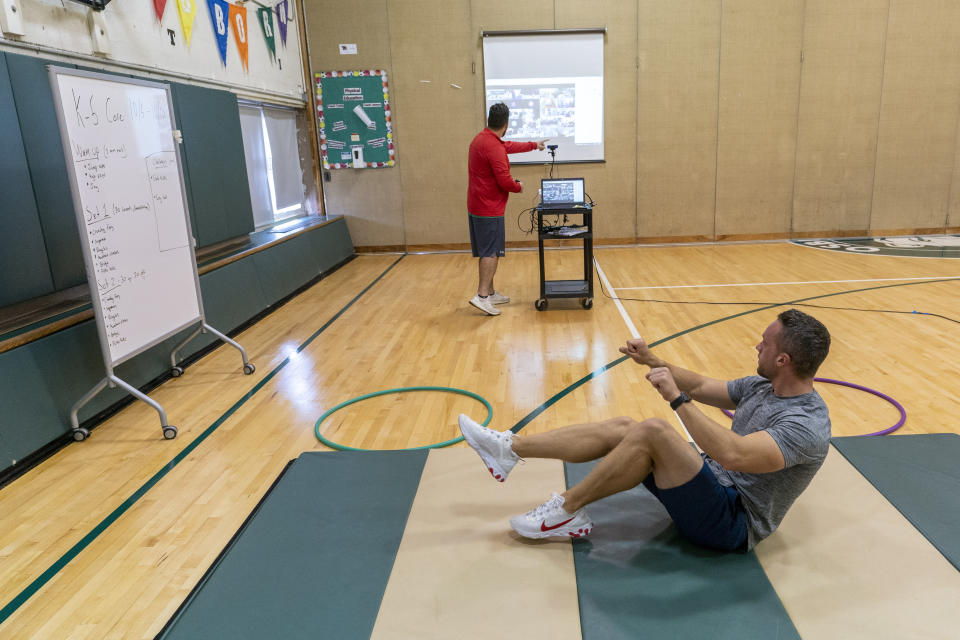 Physical education teachers Jonathan Tuttle, bottom, and Steven Lennon teach a class remotely from the gym at the Osborn School during the coronavirus outbreak, Tuesday, Oct. 6, 2020, in Rye, N.Y. (AP Photo/Mary Altaffer)