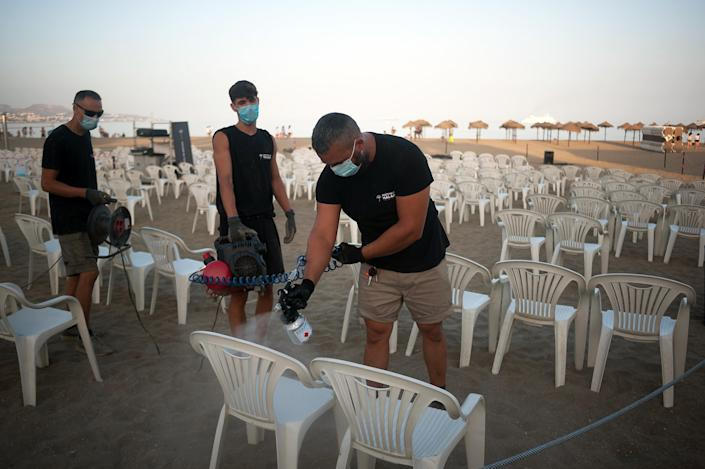 Workers disinfect chairs before the screening of a film at La Malagueta beach in Malaga, Spain. (PA)
