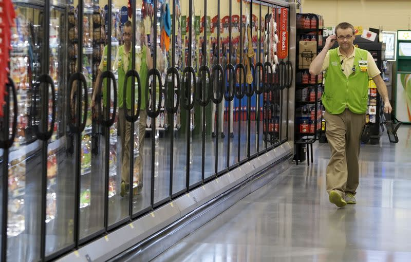 FILE PHOTO: A Wal-Mart employee is reflected in the cold cases at the Wal-Mart Neighborhood Market in Bentonville