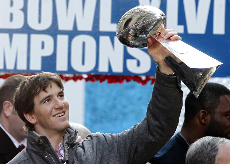 In this Feb. 7, 2012 file photo New York Giants quarterback Eli Manning holds up the Vince Lombardi Trophy during the team's NFL football Super Bowl parade in New York. Manning, who led the Giants to two Super Bowls in a 16-year career that saw him set almost every team passing record, has retired. The Giants said Wednesday, Jan. 22, 2020 that Manning would formally announce his retirement on Friday. (AP Photo/Julio Cortez, file)